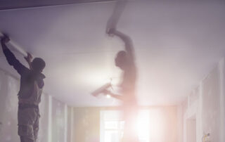 Photo of two men working on a ceiling.